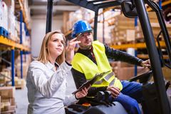 Young warehouse workers working together. Young workers working together in a warehouse stock photo