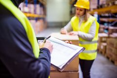 Young warehouse workers working together. Man and women discussing something, making notes Royalty Free Stock Images