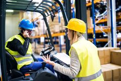 Young warehouse workers working together. Man with a smartphone, making a phone call and women holding notes, checking something Royalty Free Stock Image