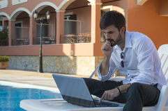 Young warried  businessman working on his laptop by the pool whi Stock Photo