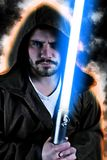 Young warrior with brown hooded cape holding a laser sword. Isolated on black background Royalty Free Stock Photography