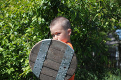 Young warrior with buckler. Boy playing role of young warrior with buckler Stock Photo