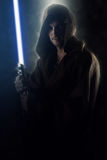 Young warrior holding a lightsaber. Over a dark background stock photography