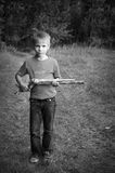 Young warrior with stick. Cute little boy with a wooden stick, young warrior, black and white artistic image royalty free stock photo