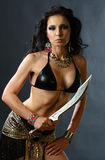 Young warrior woman. Studio shot of young warrior woman holding sword in her hand Stock Image