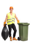 Young waster collector emptying a trash can Stock Photo