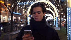 Young casual dressed man browsing his cellphone on a busy urban street at night. Young wearing casual man commuting to work while browsing his cellphone on a stock footage