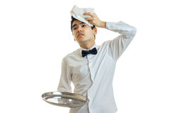 The young weary waiter holding a tray is empty and put on the head of a towel Royalty Free Stock Photography