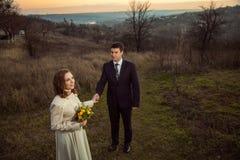 Young wedding couple enjoying romantic moments in autumn lake. Stock Photos