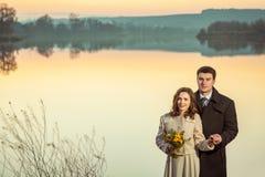 Young wedding couple enjoying romantic moments in autumn lake. Royalty Free Stock Photos