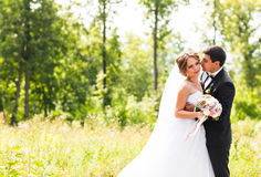 Young wedding couple enjoying romantic moments outside on a summer meadow Royalty Free Stock Photos