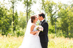 Young wedding couple enjoying romantic moments outside on a summer meadow Stock Photography