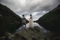 A young wedding couple enjoys a mountain view on the shore of a lake Morskie Oko stock images