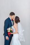 Young wedding couple kissing against a gray wall Royalty Free Stock Photography