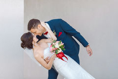 Young wedding couple kissing against a gray wall Royalty Free Stock Photos