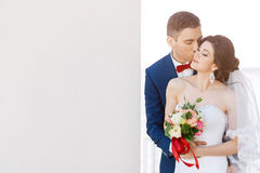 Young wedding couple kissing near a gray wall Royalty Free Stock Photo