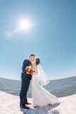 Young Wedding Couple Kissing on Pier Stock Images