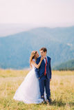 Young wedding couple posing on sunny field with distant forest hills as background. Beautiful bride is going to kiss her handsom g. Room Royalty Free Stock Image