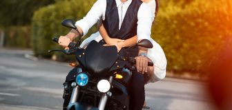 Young wedding couple riding black motorcycle in the city royalty free stock image