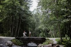 young wedding couple running on bridge above mountain river royalty free stock photography