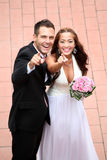 Young wedding couple showing Royalty Free Stock Images