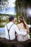 Young wedding couple sitting on a bench. Photo of a young couple soon to be married, sitting on a bench beside a lake and beautiful country scenery Stock Images