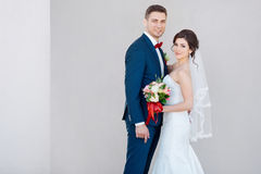 Young wedding couple smiling against a gray wall Royalty Free Stock Images