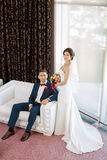 Young wedding couple on sofa against a window Stock Images