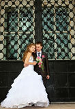 Young Wedding couple stand near huge gate Royalty Free Stock Images