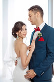 Young wedding couple standing against a window Stock Photos