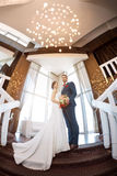 Young wedding couple standing against a window Stock Images