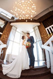 Young wedding couple standing against a window Royalty Free Stock Images