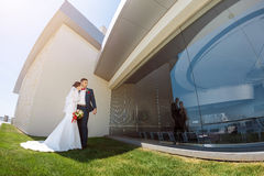 Young wedding couple standing outdoors Stock Photo