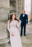 Young wedding couple standing outside near atique building with columns.  Royalty Free Stock Photography