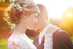 Young wedding couple on summer meadow. Young wedding couple enjoying romantic moments outside on a summer meadow