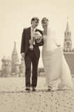 Young wedding couple walking. On Red Square. Retro colors Royalty Free Stock Image