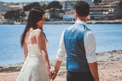 Young wedding couple walking on the beach stock images