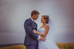 Young wedding couple walking on field. Stock Image