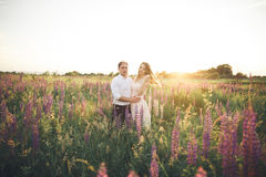 Young wedding couple walking on field with flowers Royalty Free Stock Images