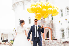 Young wedding couple walking outdoors with balloons Stock Photo
