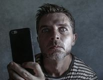 Young weird and crazy mobile phone addict man using cell compulsively with weird and freak face expression in internet social. Media addiction and obsession on stock photos