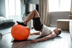 Young well-built man go in for sports in apartment. Guy hold legs on fitness ball and doing lifting up with body. Strong stock image