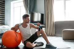 Young well-built man go in for sports in apartment. Serious concentrated guy lean to big red fitness ball. He hold blue stock image