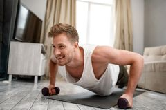 Young well-built man go in for sports in apartment. Strong muscular guy stand in plank position using dumbbells and look. Forward. He use all his strenghts stock photos