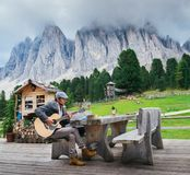 Young well-dressed man, 30-35, playing a guitar with Italian Dolomites rock formation background. Dolomites, Italy - September 9th, 2017: Young well-dressed man royalty free stock photography