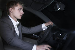 Young well-dressed man in a suit is sitting in his car before going on a night out in Beijing Stock Photo