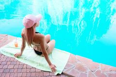 Young wet girl in black bikini sits with arms behind her back, a. T the edge of the swimming pool, relax, and drink orange juice Royalty Free Stock Photo