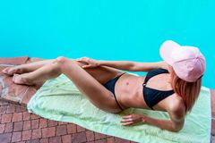 Young wet girl sunbathing next to the pool, in black swimsuit an. D pink hat Royalty Free Stock Image