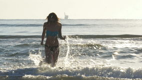 Young wet woman running in the waves of the sea towards the shore. Young woman running in the waves of the sea towards the shore stock video