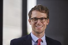 Young white businessman wearing glasses smiling, close up Royalty Free Stock Photos